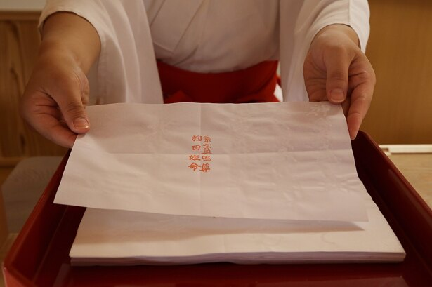 神札授与所で巫女から占い用紙(100円)を受け取り、いざ奥の院・鏡の池へ