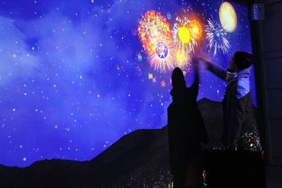 ネイキッドによる特別展示。壁面に投影された惑星に触ると、映像が変化するデジタルアート