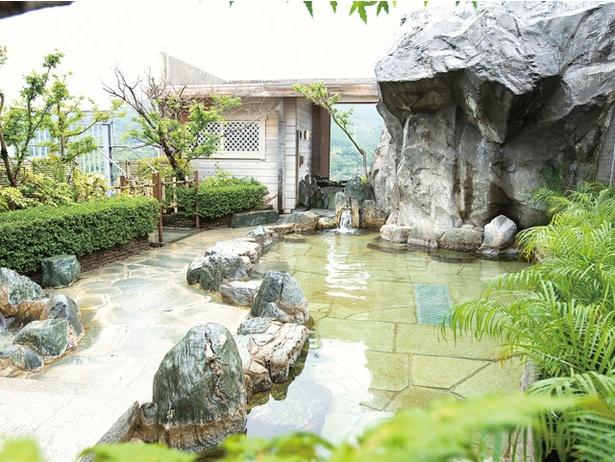 【写真を見る】ホテル桜 / 野趣あふれる露天岩風呂。奥にサウナや水風呂も備える