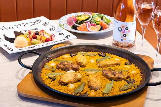 写真のパエリアはパエリア発祥の地、バレンシアの伝統を受け継ぐ「バレンシア風」(2名分)。ウサギや鶏肉の旨味を米にうつしエスカルゴやインゲンなどの食材を加えるのがバレンシア風