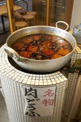 店内に置かれた大きな鍋で名物の「肉豆腐」を作る。甘辛いタレの香りが食欲をそそる。1皿410円で、煮玉子入り(518円)もある