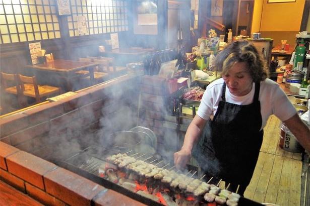 気さくな女将、吉田さんが手際よく炭火で焼いてくれます(店内の様子は移転前の旧店舗です)