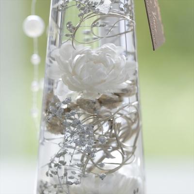 繊細なプラチナゴールドの花材やボトルの底にあるシルバーのカラーサンドが、白い花の輝きを演出する