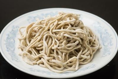麺は加水率36%の硬い生地を何度も手で打つことで強いコシを生む。縮れ麺でスープとの絡みも良好