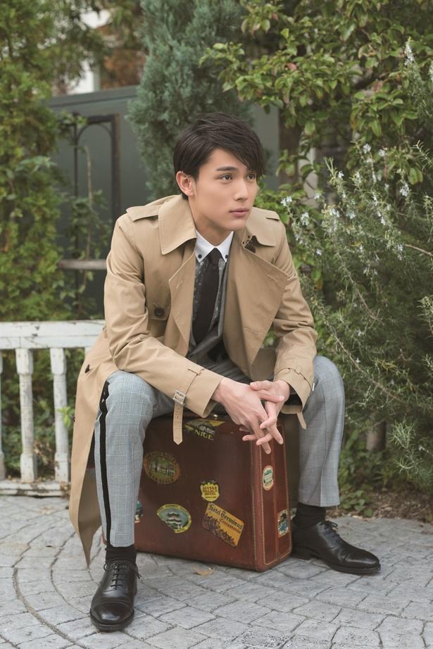 旅行かばんに腰を下して佇む