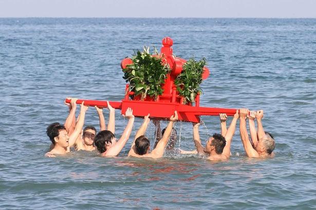海上で男達が朱塗りの神輿を高く掲げる