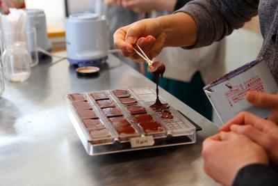 カカオ豆からチョコレートを作る、Minimalのワークショップ。写真はチョコレート生地を型に入れる作業