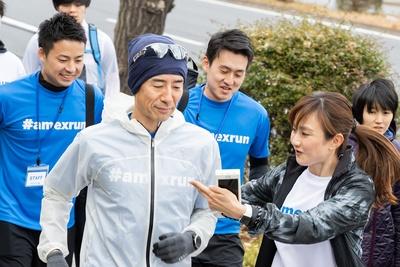 走るランナーに声をかける湯田さん(右)