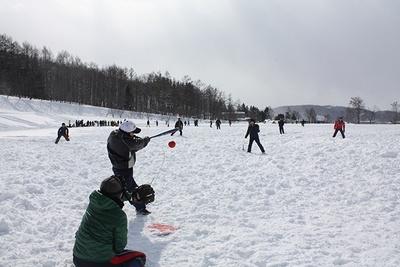 雪原でもひと目で分かるよう、塗料で赤く塗られたボールをフルスイング!