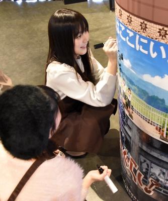 壁のポスターにサインを書く間島和奏さん