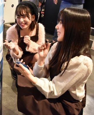壁のポスターにサインを書く間島和奏さんと長月翠さん