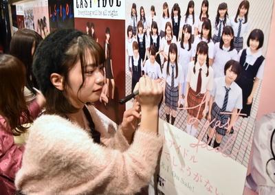 ポスターにサインを書く長月翠さん