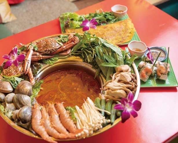 【写真を見る】カニやエビ、アサリなど豪華具材を味わうピリ辛!海鮮トムヤム鍋(1人前1598円、手前、写真は4人前)。名物のバインセオ(842円、奥)など/ベトナム屋台酒場 デンロン