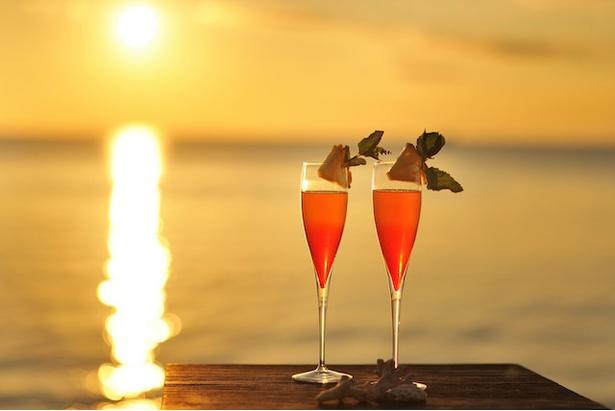星のや竹富島 / 「サンゴ砂の島夕日ツアー」。ビーチチェアと夕日をイメージしたパッションフルーツのカクテル