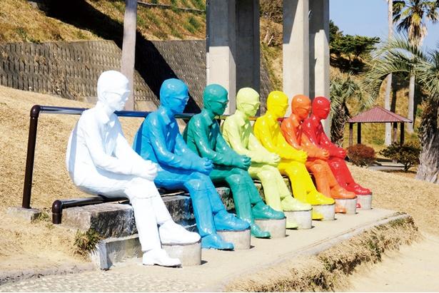 足を組んだポーズで、7色7体の像が一列に並ぶ / サンメッセ日南