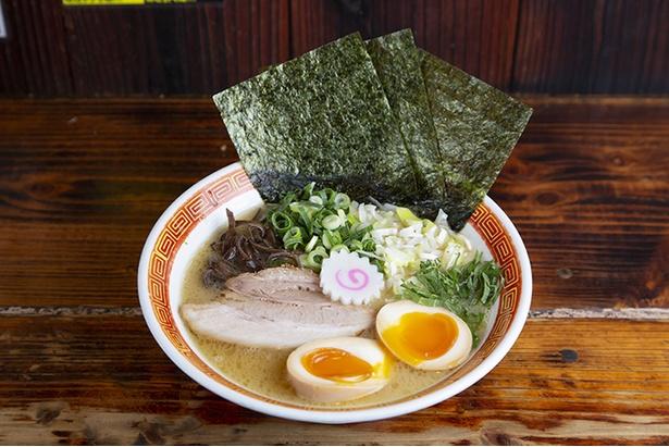 特製豚骨ラーメン(780円)。大量の豚骨と鶏ガラを大釜で炊いたスープは濃厚でコラーゲンもたっぷり。特製は味玉、 海苔3枚、大葉、白ネギがのる