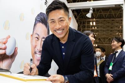 笑顔でサインを書く前園さん