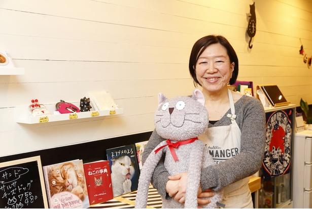 オーナーの矢口憲子さん。普段はレジ横でお出迎えしてくれるネコのぬいぐるみと一緒に