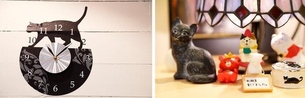 文字盤&ネコの絵が壁に直接描かれた時計(写真左)。さまざまなテイストのネコの置物が。プレゼントされたものも多いとか(同右)