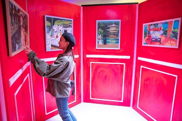鏡が一切なく、赤い壁に絵が飾られたスペースも