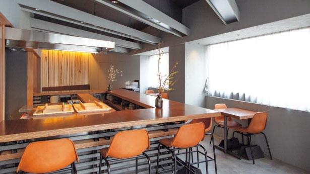 素材感を生かしたグレーと木目のシックな店内。調理のライブ感とスタッフとの会話が楽しめるカウンター12席、テーブル12席も