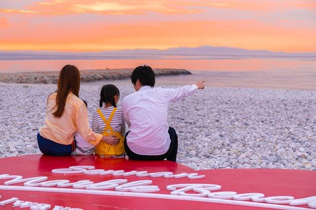 目の前のマーブルビーチでは、白い玉石と青い海、赤い夕陽の鮮やかなコントラストが