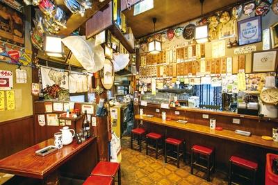 壁には手書きのメニューのほか、全国各地のみやげ物や店主が撮影した写真がいっぱい / 串やき 五條 名驛