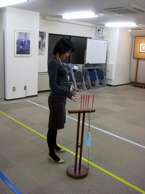 的に対して斜め45度程度に立ち、足を肩幅に開いて筒の吹き口に矢を入れる