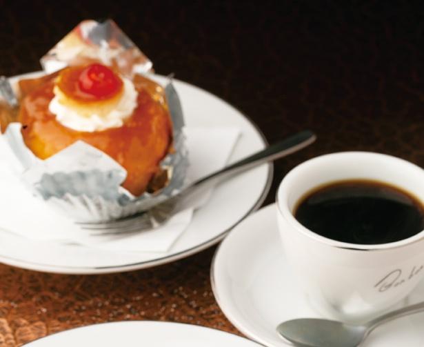 生地にラム酒を染み込ませた「サバラン」(左奥、270円)も人気のケーキ。昔ながらのケーキと共に味わいたい「ブレンドコーヒー」(右前、350円)