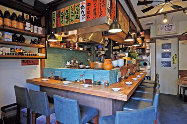 レトロ感のある店内には、カウンター席のほかグループで使えるテーブル席も。壁にはスッポンにちなんだイラストなどがはられている/蛸焼とおでん 友の
