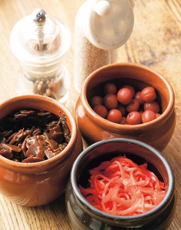 【写真を見る】薬味はツウ好みのニンニク佃煮や小梅、定番の紅生姜、白ゴマ、胡椒の5種がテーブルに/ら~めん ばっこ志
