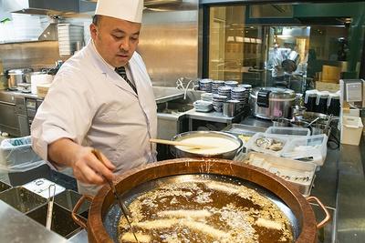 職人が黄金色の香ばしい天ぷらに仕上げる。店内には香ばしい油やタレのにおいが漂い、食欲を刺激する