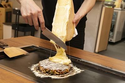 溶けたチーズを目の前でお好み焼きにかけてくれる。1かけするだけでも満足な量!