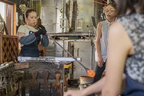 1200度にもなる炉の中で高温融解したガラスを吹き竿と呼ばれる金属のパイプの先に巻き取り、反対側から息を吹き込んでガラスを形成していく
