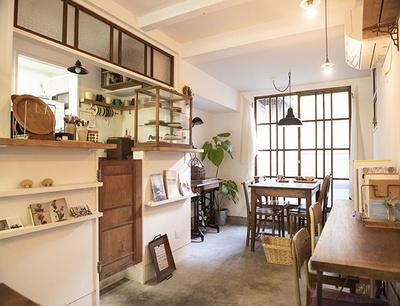 【写真を見る】陽光が優しくそそぎ、アンティーク家具、古いミシンなどを配したリラックスできる空間