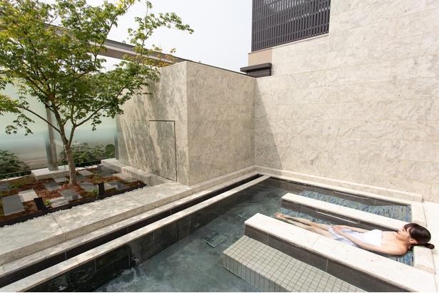 空を眺める開放的な寝湯 ※撮影のためバスタオルを着用しています