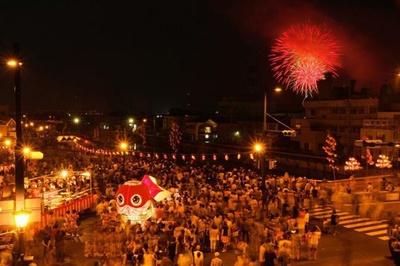 柳井金魚ちょうちん祭り / 金魚ちょうちんが飾られた白壁の背景を花火が照らす