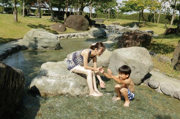 【写真を見る】自然石を配置した渓流や噴水がある「けい流・子供プール」で水遊び/京都府立 山城運動総合公園 太陽が丘ファミリープール