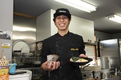"""看板メニューの「葉、薫るつけ麺」を差し出す店主の永濱春樹さん。""""ヌードルクリエーター""""を名乗り、創作麺を日々考案する"""
