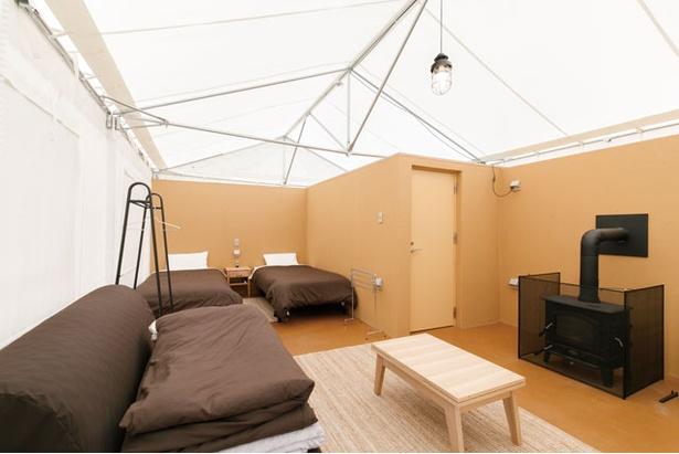【画像を見る】室内にはベッド、ソファベッド、ハンガーラックがある。薪ストーブも備えるので冬キャンプも安心 / モンベル五ヶ山ベースキャンプ