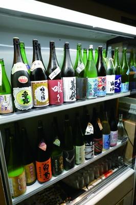【写真を見る】ショーケースから自由にお酒を選べる。ケースごとに西日本と東日本の銘柄に分けられている/日本酒×発酵 八光(はちみつ)