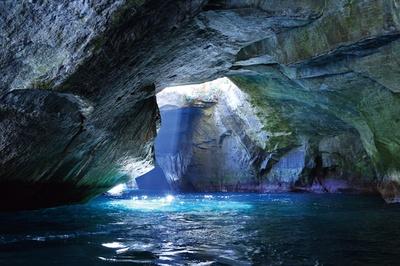 【写真を見る】洞窟の上から光が射し込み、海面を照らす / 堂ヶ島天窓洞