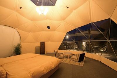 【写真を見る】ドーム型テント「ラグジュアリー」は、大きな窓が開放感抜群。冷暖房完備のテント内でゆったりしよう。外側のテラスではBBQもできる