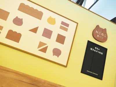 かわいらしい雰囲気の店内の「NEKO NEKO SHOKUPAN」。壁面のボードには、パンの焼き上がりの時間が掲示される /「オアシスパーク」