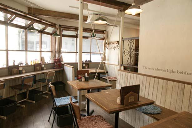 木のテーブルに学校の椅子などが置かれたほっこりとした空間。駅からすぐの立地も便利/OSORA CAFE