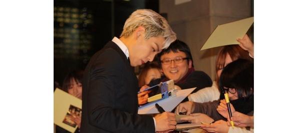 【写真をもっと見る】ファンにサインをするチェ・スンヒョン
