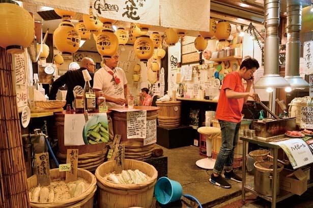 樽のテーブルが並べられた店内は、ぬかの香りに包まれている。店頭で販売している焼きたての牛串も人気/立ちのみ 賀花