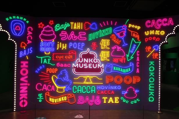 東京の「うん語ネオンゲート」はLEDを用いることで明るさがアップ。うんこを意味する様々な国の言葉が並ぶ