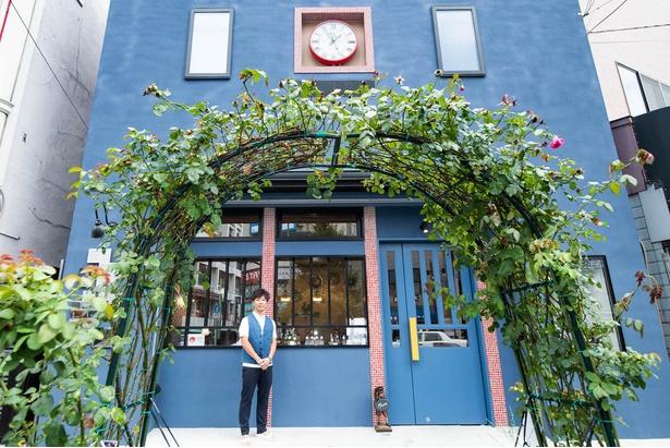 紺碧の外壁が鮮やかな建物の前には、バラの木のアーチが架かる。大きな壁時計が街を見下ろす