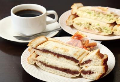 コーヒー(奥左410円)などすべてのドリンクに付く無料サービスは6種類。小倉あんプレスサンド(手前)や、野菜サラダプレスサンド(奥右)が好評 / モーニング喫茶 リヨン